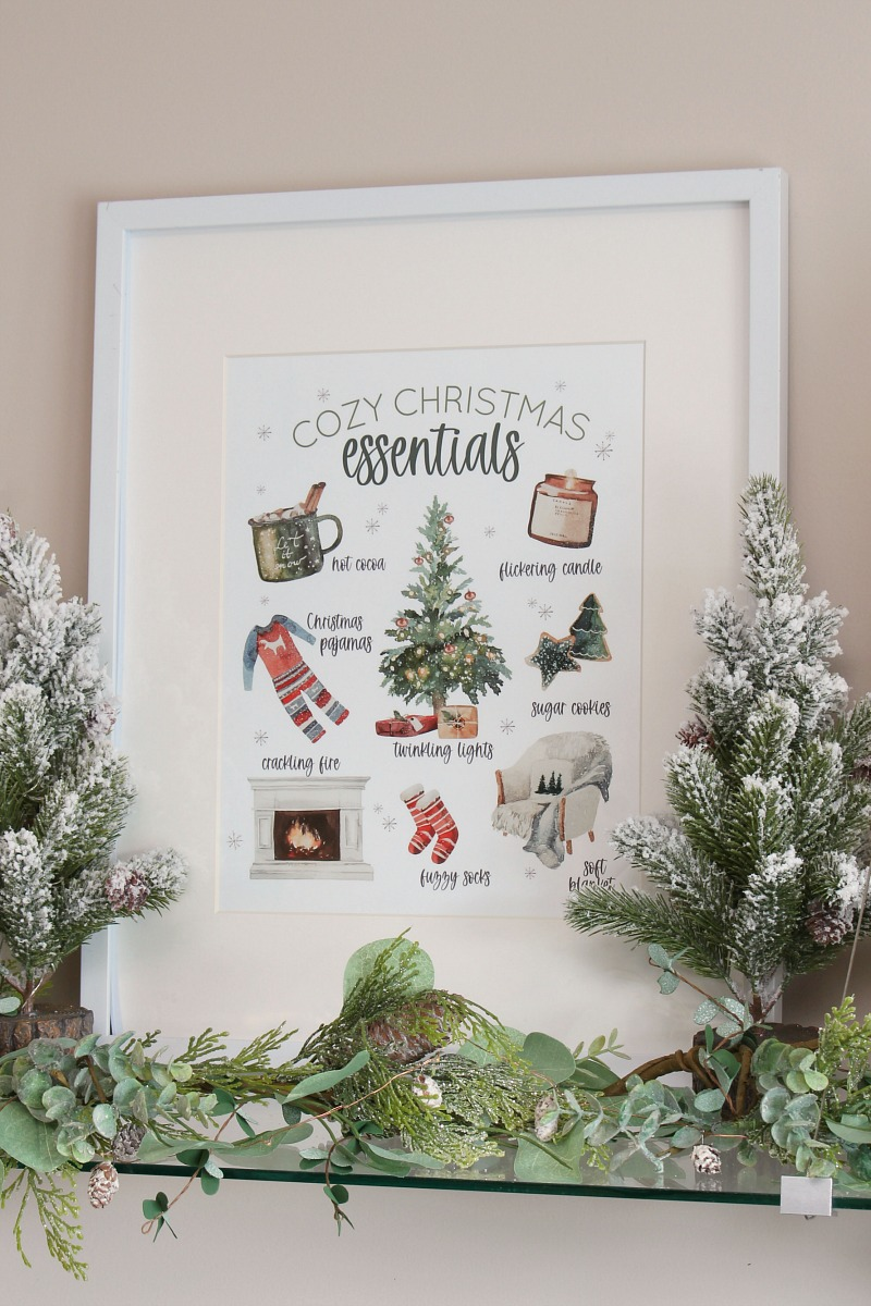 Cozy Christmas Essentials free Christmas printable in a frame with flocked trees.