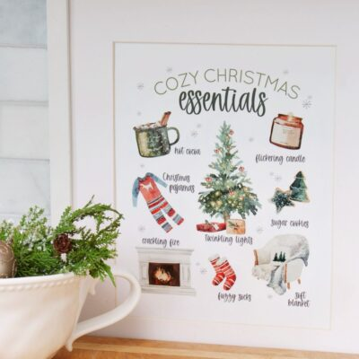 Cozy Christmas Essentials free Christmas printable in a frame with a bowl of ornaments.