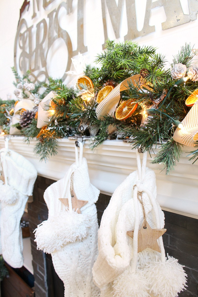 Beautiful neutral Christmas mantel with dried oranges glowing in the lights.