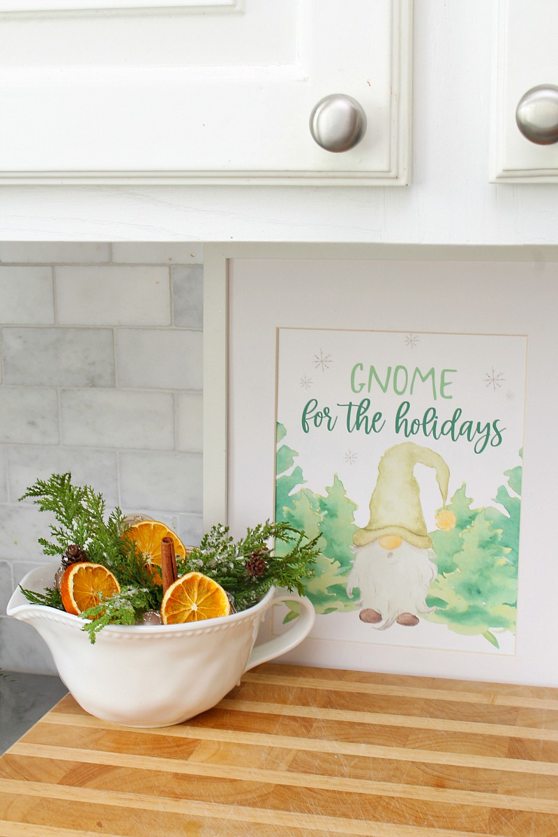 Gnome for the Holidays framed gnome Christmas printable with a bowl of greenery and dried oranges.