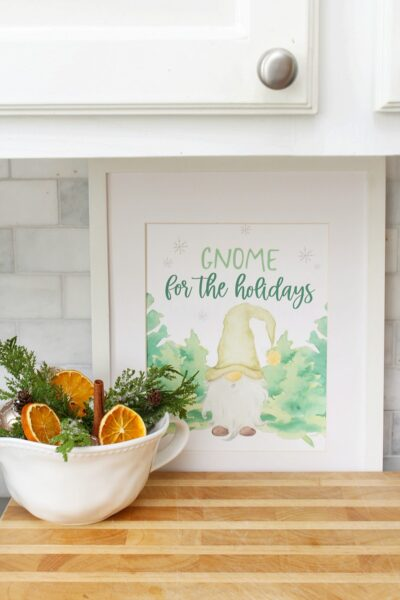 Gnome for the Holidays framed Christmas print with a bowl of greenery and dried oranges.