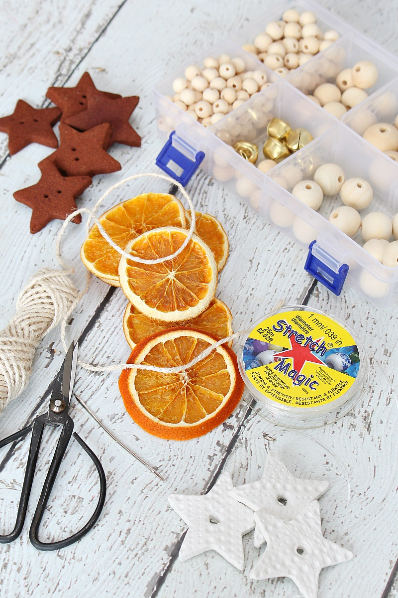 Materials for DIY dried orange garland and Christmas ornaments.