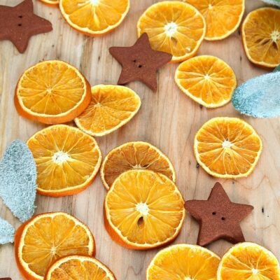 Dried orange slices with cinnamon ornaments on a cutting board.