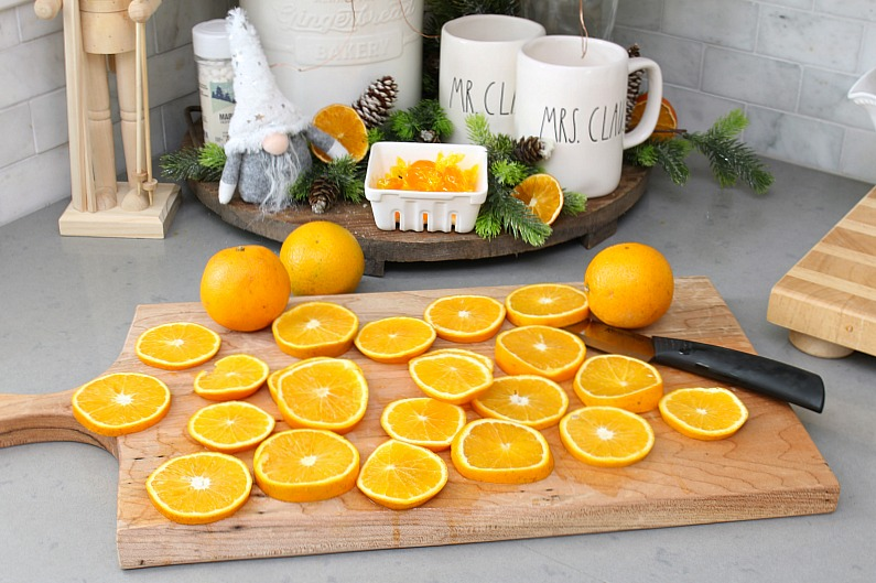 Sliced oranges on a cutting board for drying.