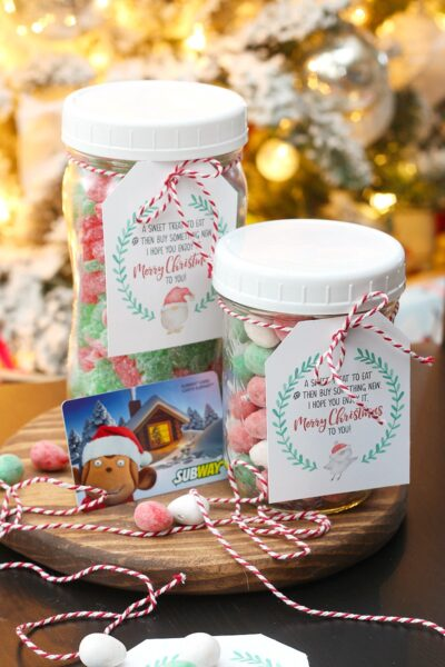 Mason jar filled with Christmas candy and a gift card with a free printable Christmas gift tag.