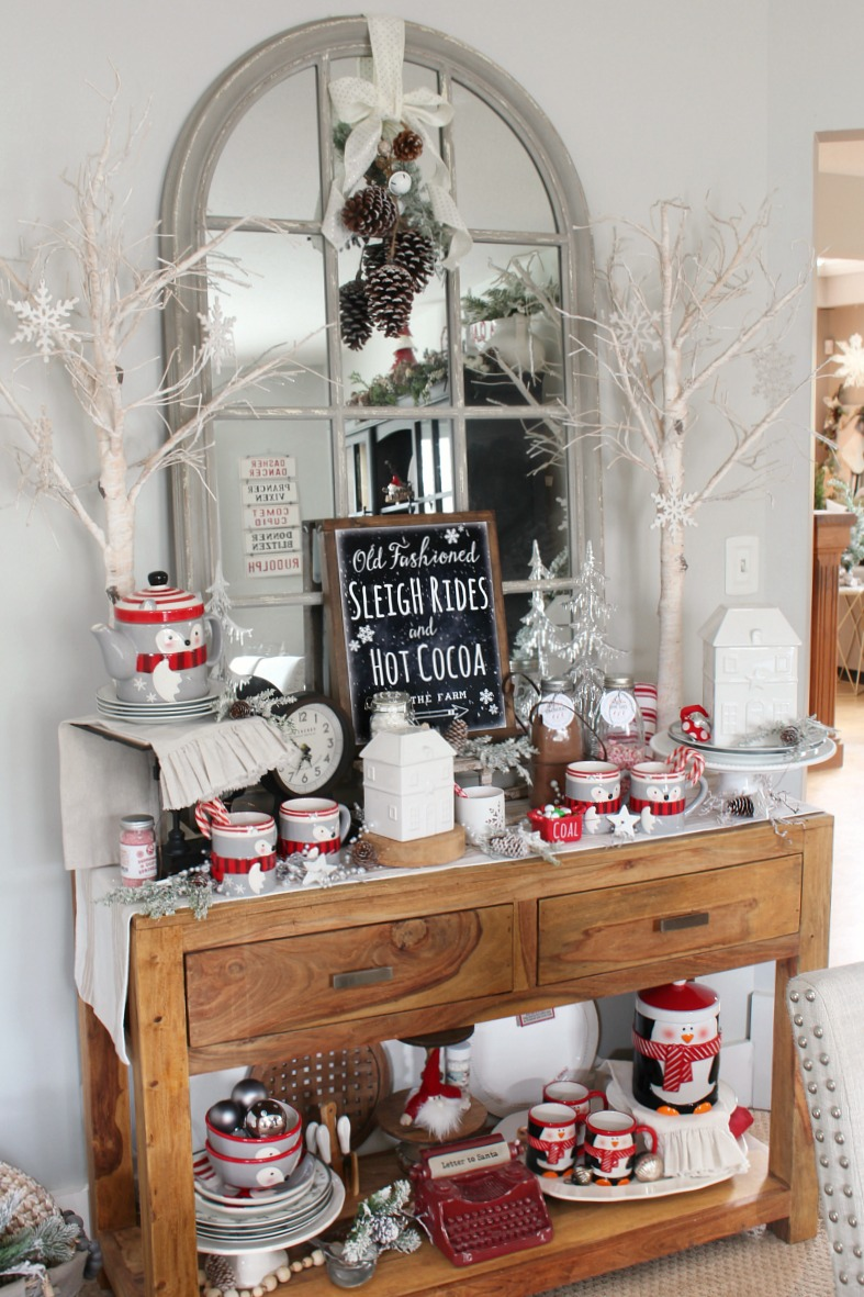 Side board in a dining room decorated for Christmas as a hot chocolate bar.