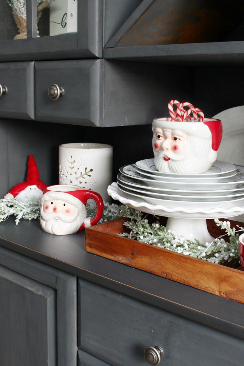 Santa Claus mugs and bowls on a dining room hutch.
