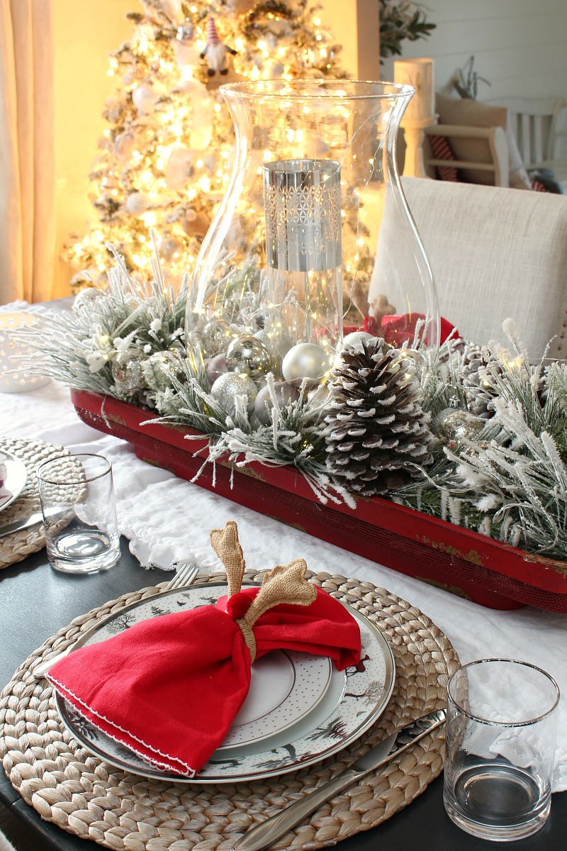 Christmas tablescape with pops of red and a glowing Christmas tree.