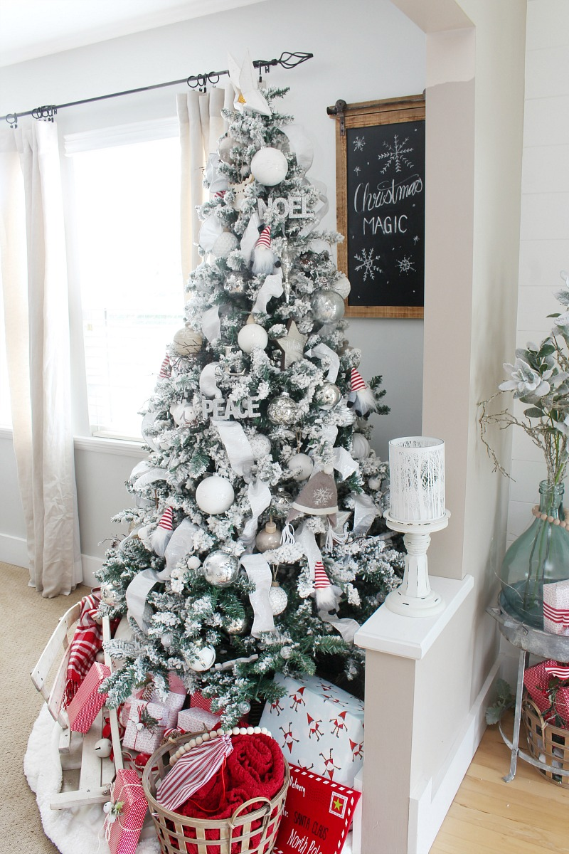 Flocked Christmas tree decorated with white and silver with a few pops of red.