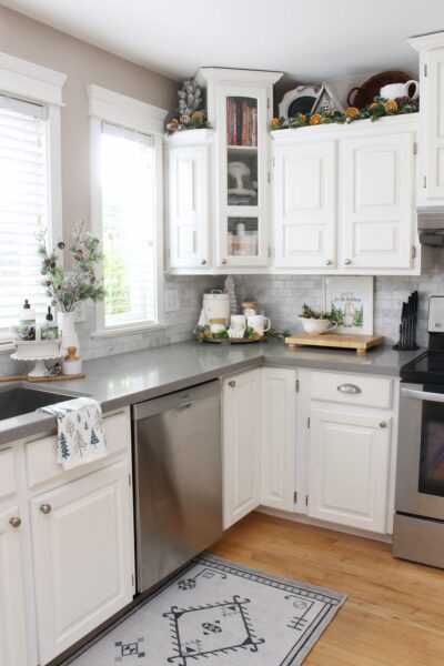 White modern farmhouse style kitchen decorated for Christmas in green and white with dried oranges.