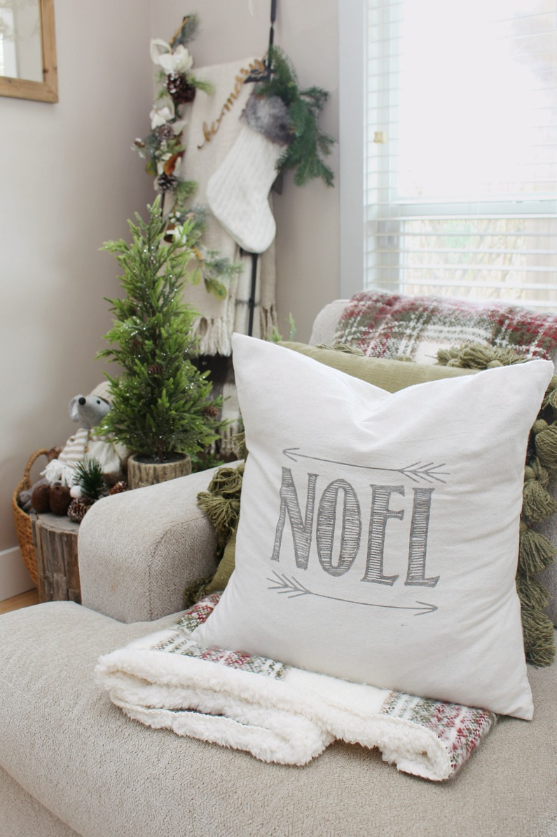 Noel Christmas pillow in a cozy Christmas living room.