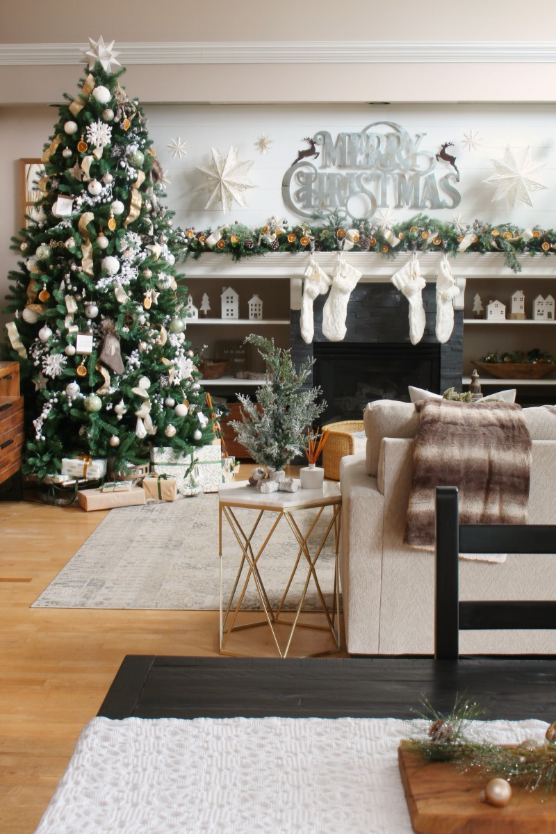 Cozy living room decorated for Christmas in greens, whites and golds with a pop of orange.