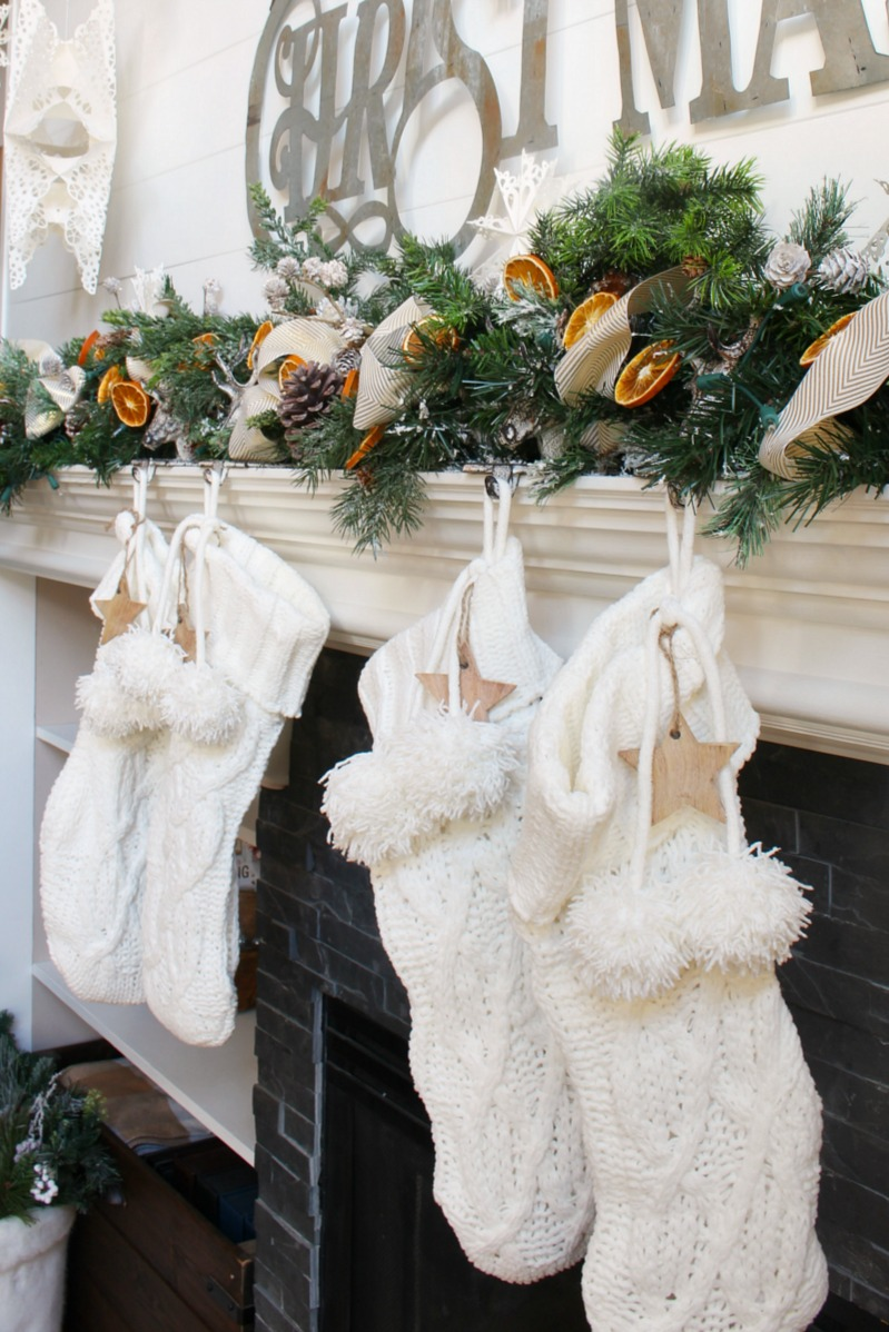 Beautiful Christmas mantel decor with greenery and dried oranges.