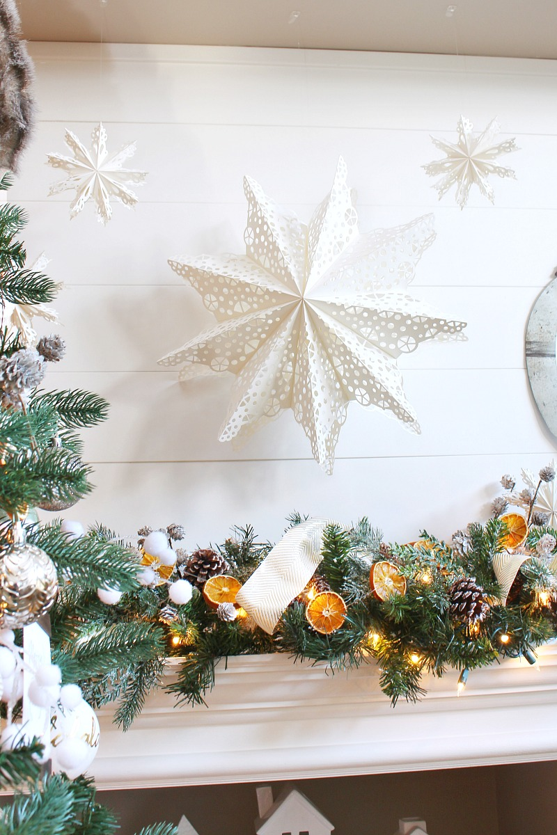 Pretty 3-D snowflakes hanging above a Christmas mantel.