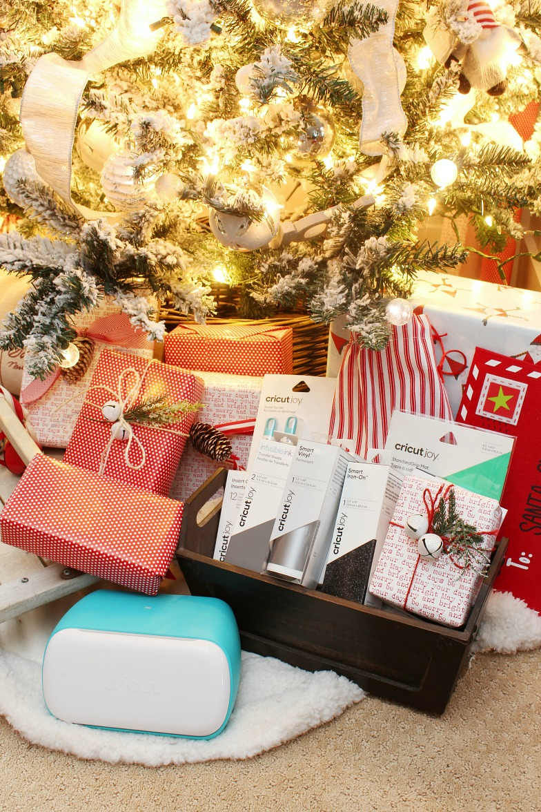 Cricut Joy and Cricut Joy gift basket in front of a glowing Christmas tree.