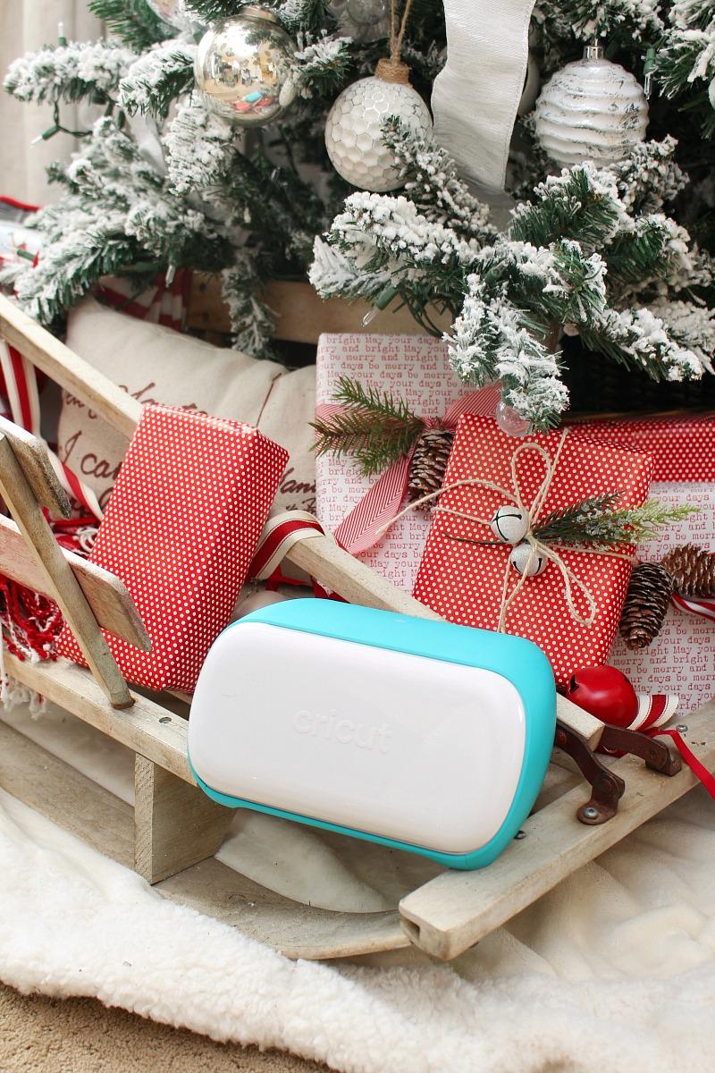 Cricut Joy machine on a sled with presents under a Christmas tree.