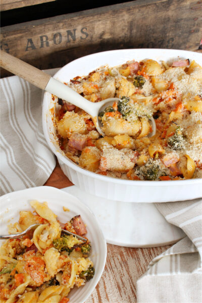Cheesy vegetable and ham casserole in a baking dish.
