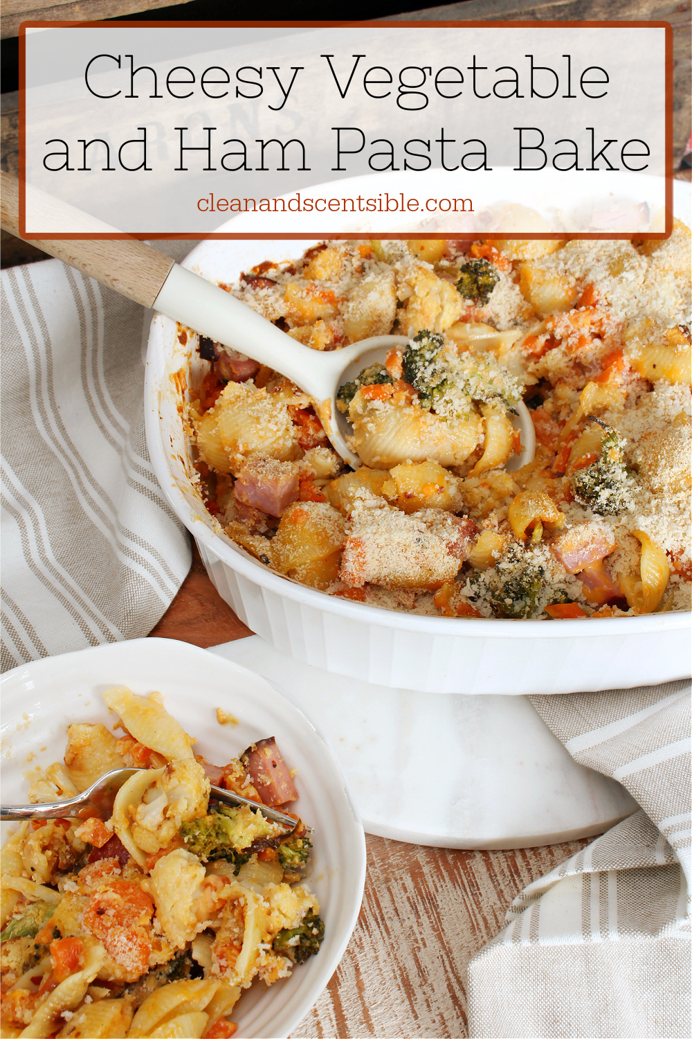Cheesy vegetable and ham pasta bake in a white Corning ware dish.