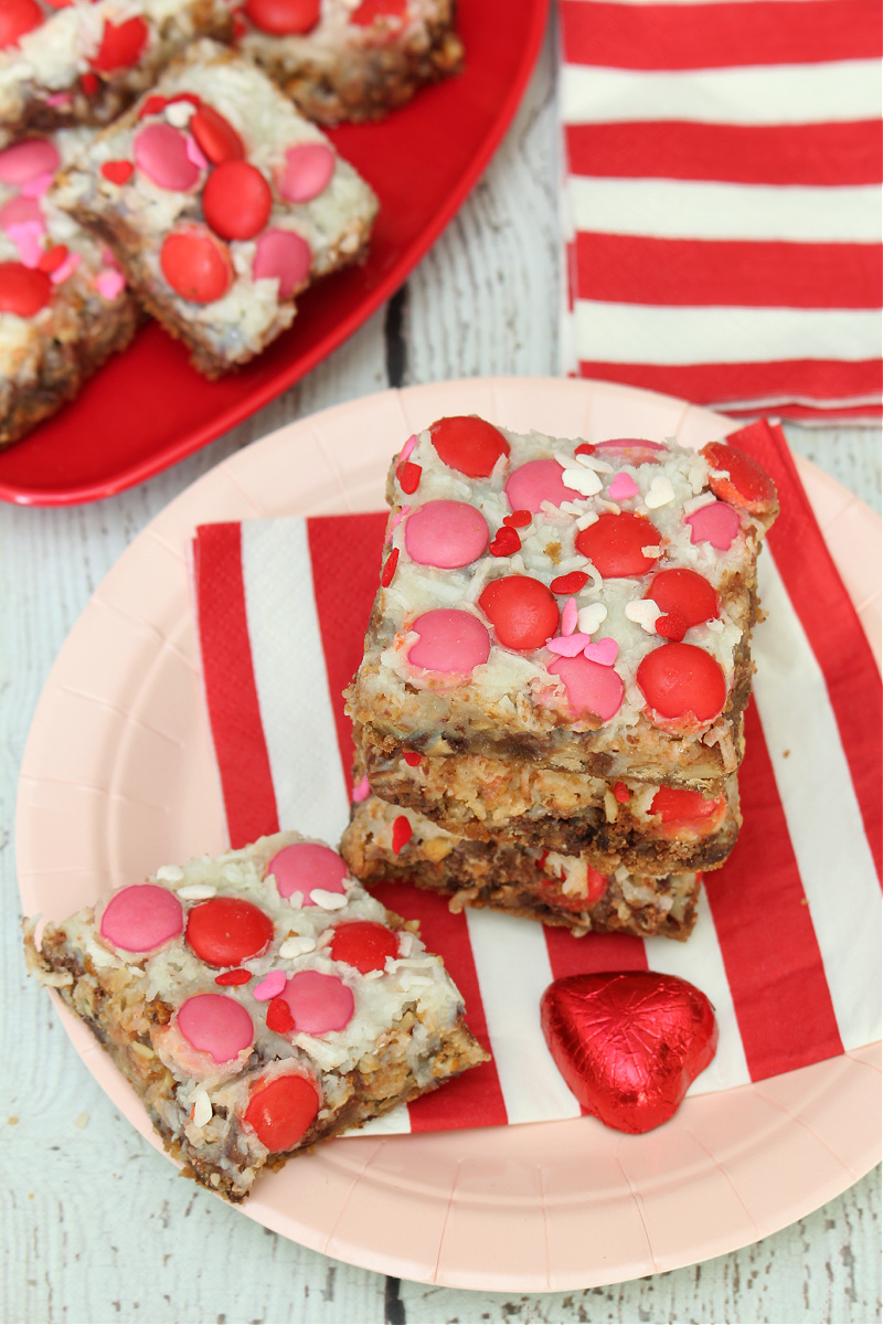 Seven layer bars dressed up for Valentine's Day with pink and red candies.