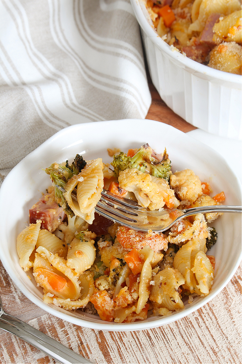 Ham and vegetable cheesy pasta bake in a bowl.