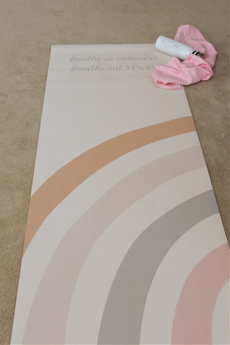 DIY custom yoga mat on a bedroom floor. with water bottle.