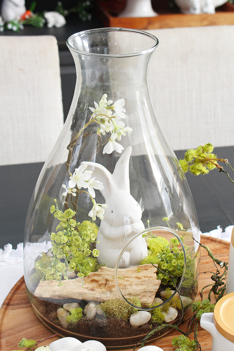 DIY Easter centerpiece in a terrarium with Easter bunnies and natural elements.