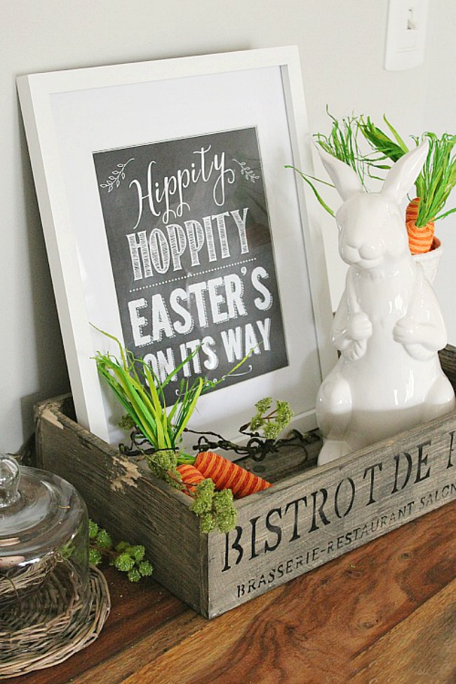 Hippity Hoppity Easter's on its Way printable displayed with a white bunny and carrots.