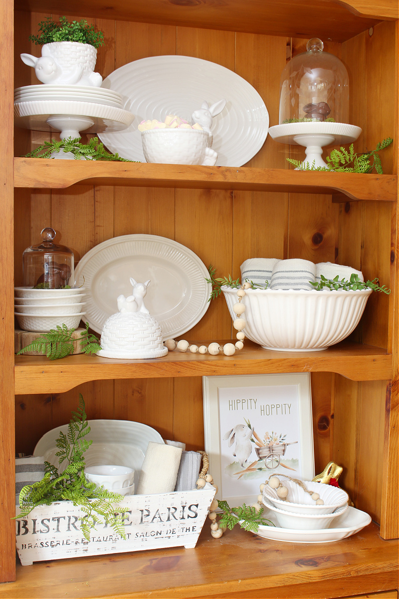 Wood hutch decorated for Easter with white dishware and white bunnies.