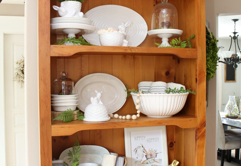 Wood hutch decorated for Easter with white dishes and Easter bunnies.