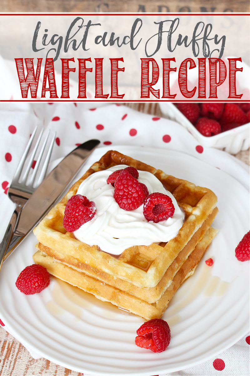 Light and fluffy waffles topped with raspberries, whipped cream, and syrup.
