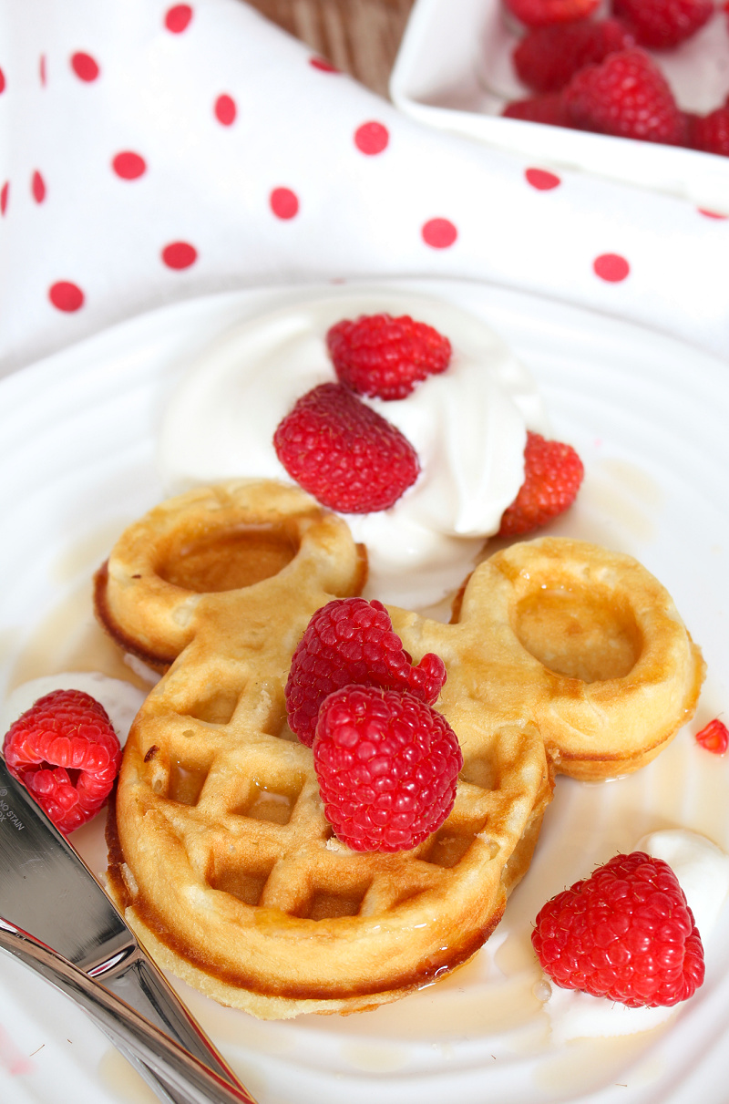 Delicious Mickey Mouse waffles topped with raspberries and whipped cream.