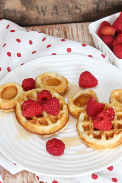 Cute mickey waffles with raspberries and syrup.