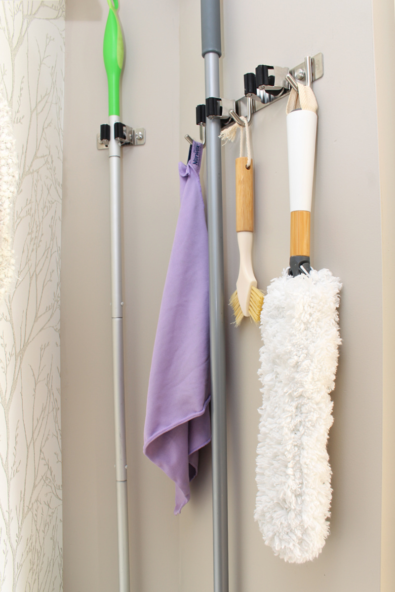 Mop and broom wall holder with hooks for cleaning supplies.