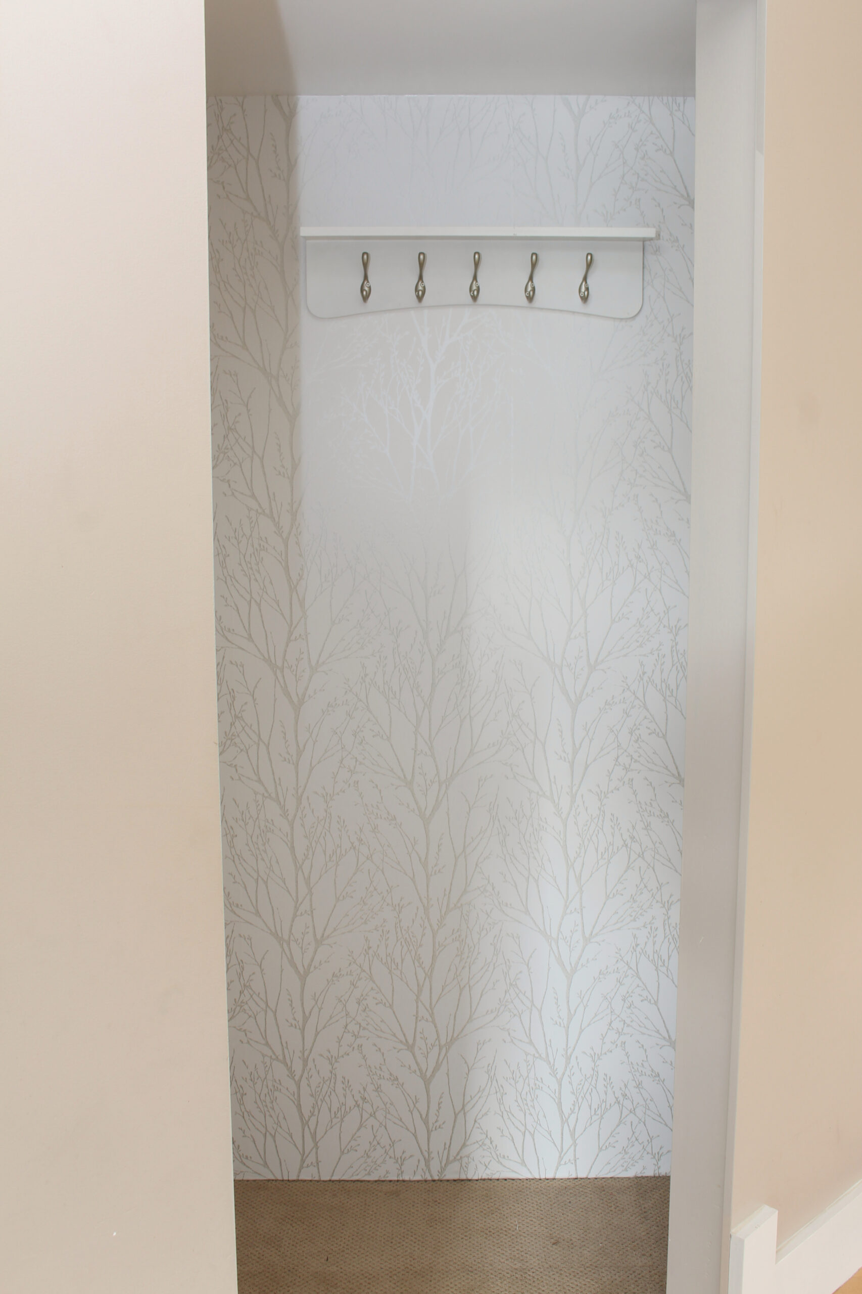 Small front entry closet decorated with peel and stick wall paper.