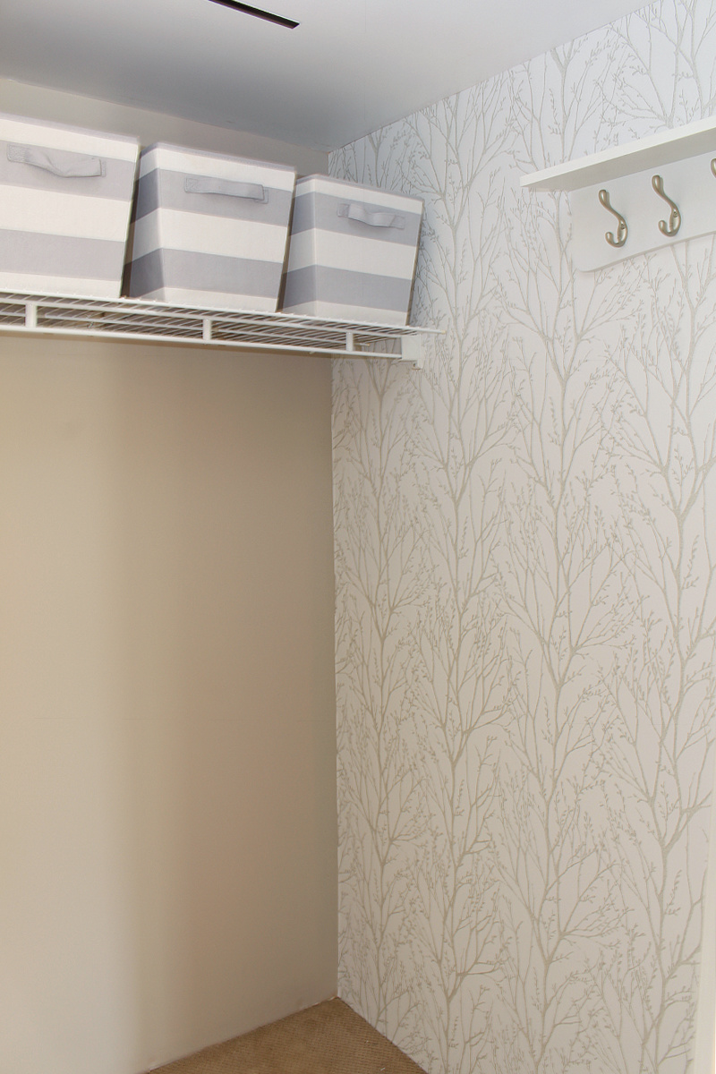 Pretty peel and stick wall paper in a front entry closet.