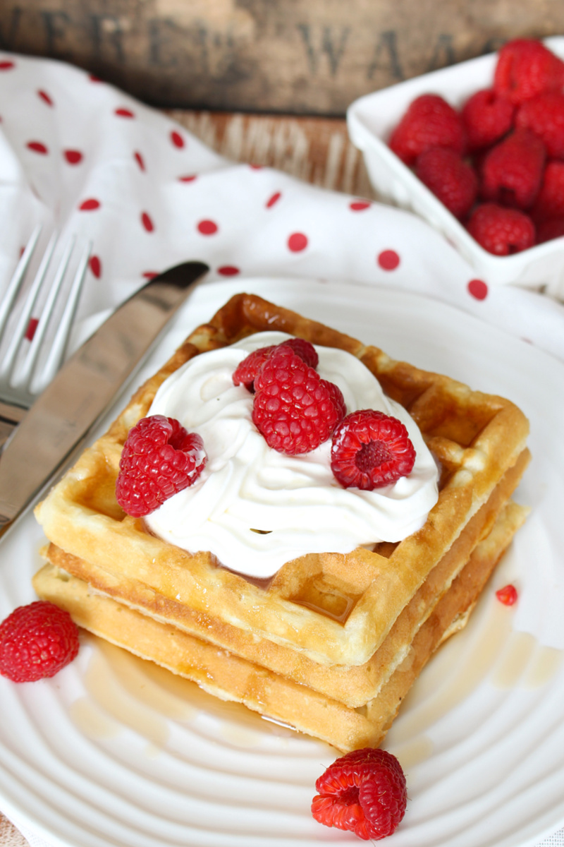 Belguim waffles with whipping cream, syrup, and raspberries.