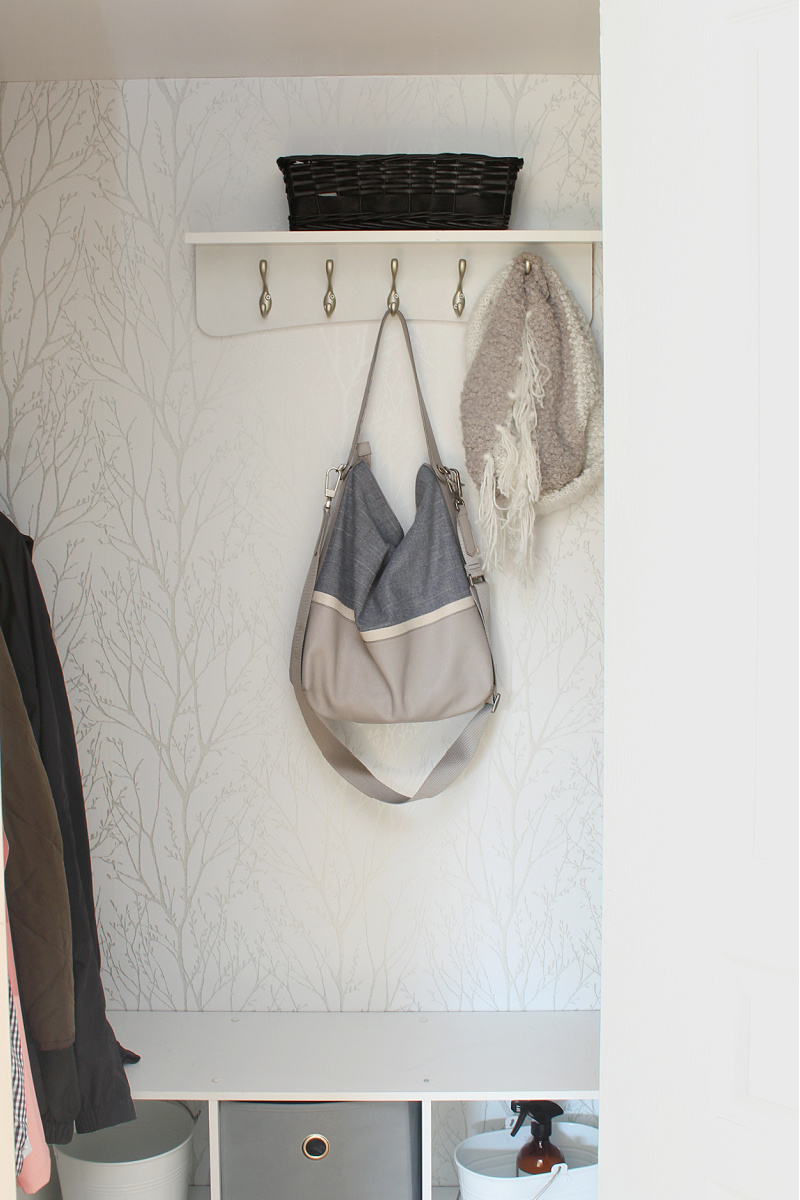 Small entry closet with hall hooks and small shelf.