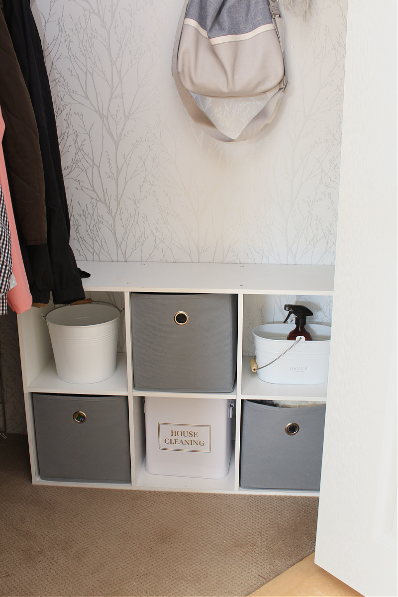 Storage cubes and bins used for extra storage in an organized small closet.