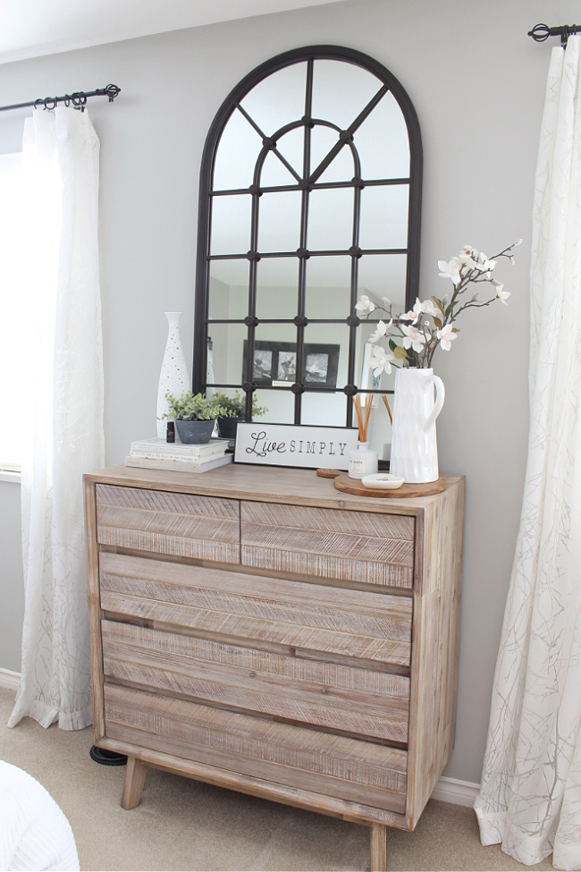 Wood dresser with black metal mirror and simple decor.