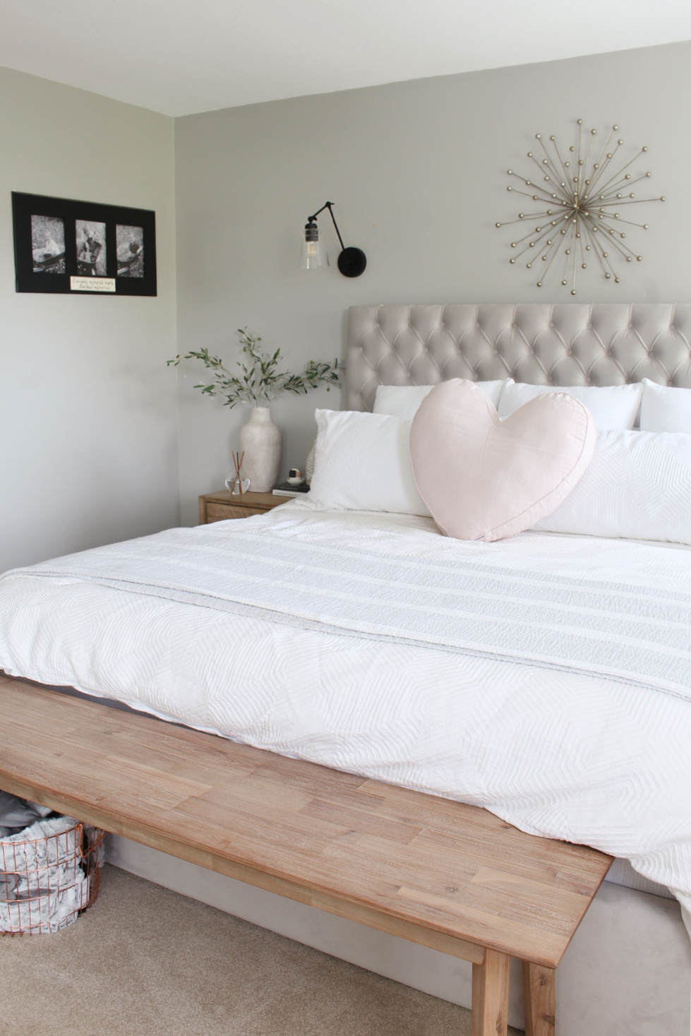 Grey upholstered bed with white bedding and a heart pillow.