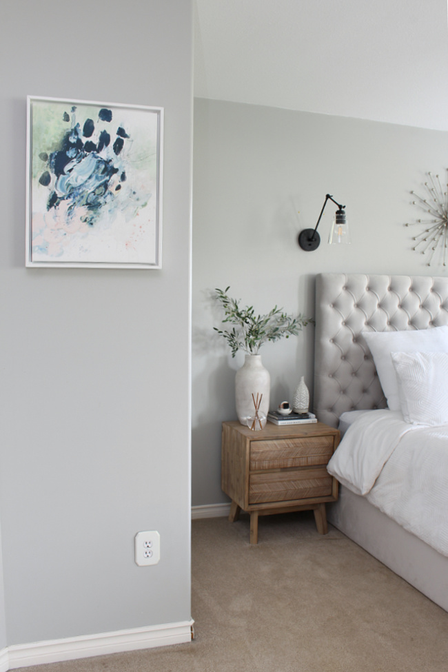 Abstract artwork in a master bedroom decorated for summer.