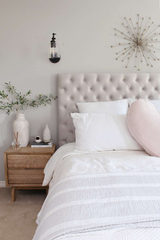 Upholstered bed with white bedding and a pink linen heart pillow.