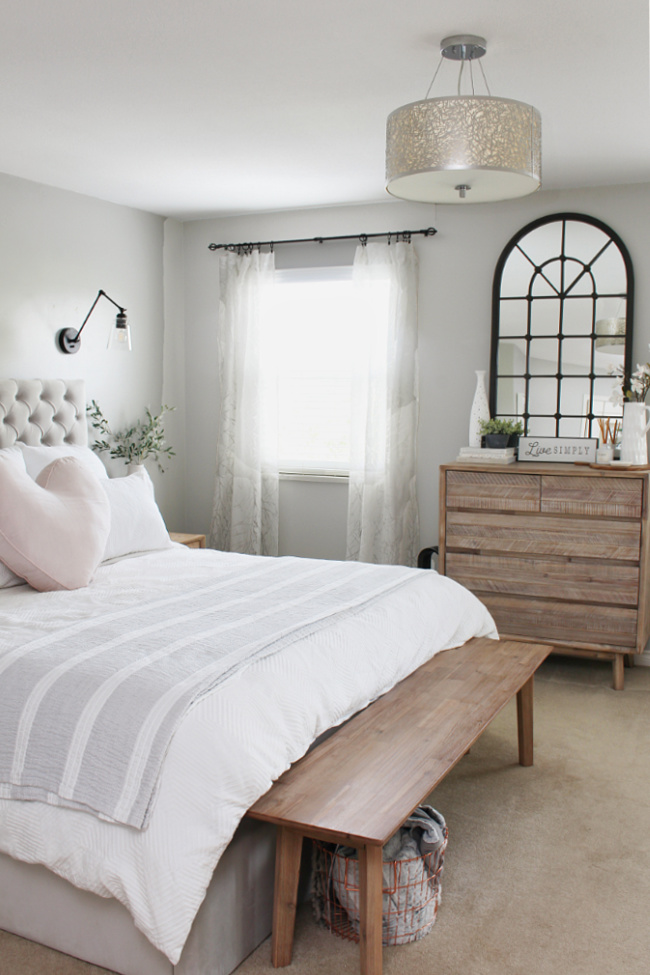 Master bedroom decorated for summer with neutrals and a pop of pink.