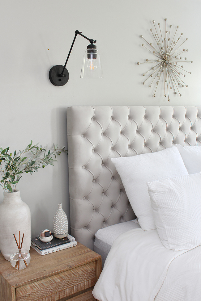 Master bedroom with an upholstered bed and wall lights.