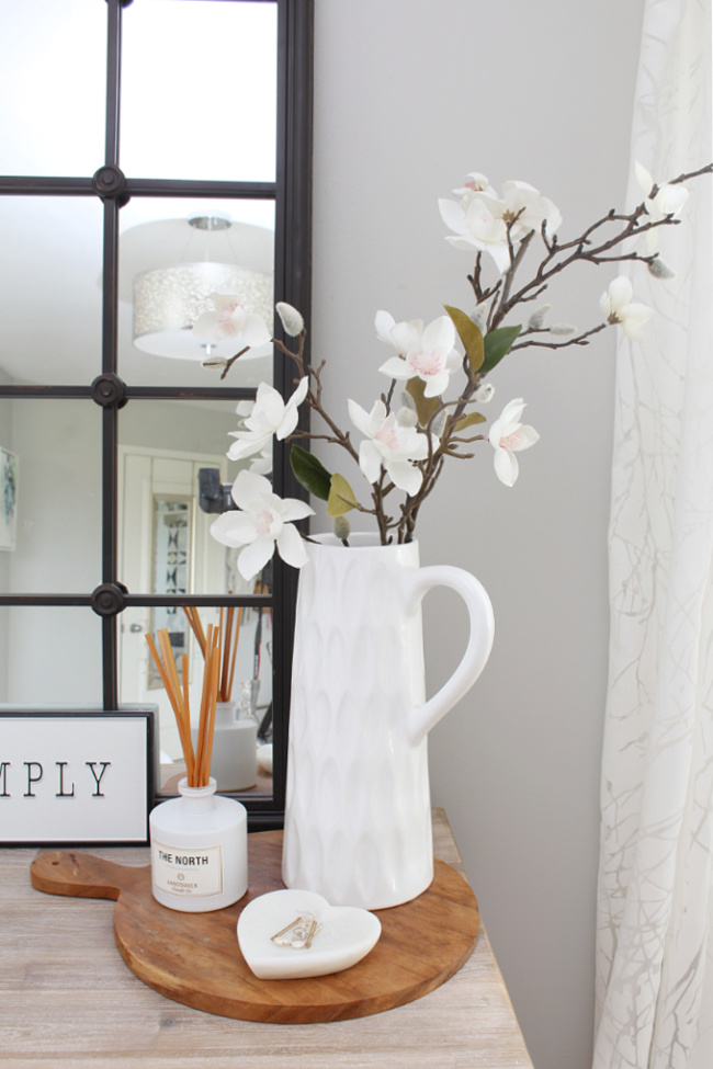 Dresser in a master bedroom decorated for summer with a white vase and faux stems.