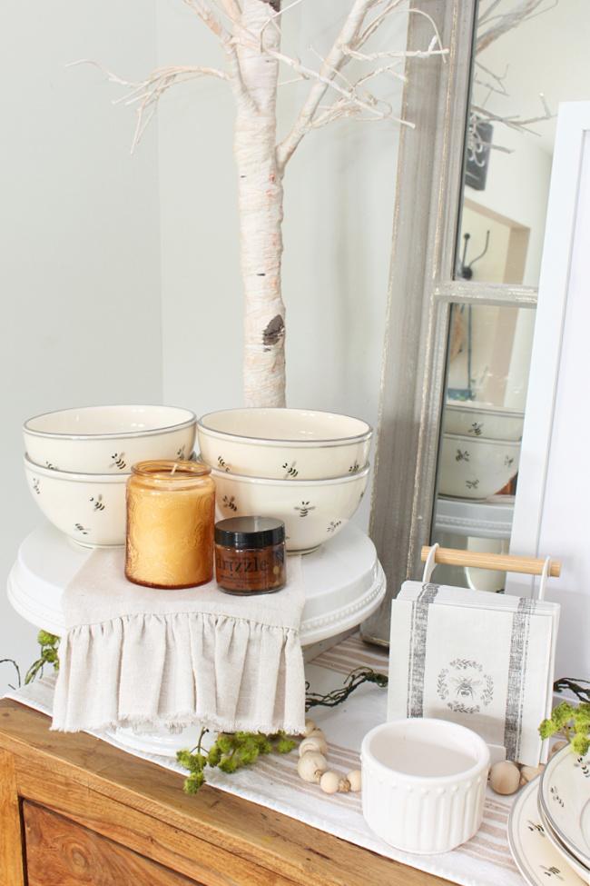 Honey bee decor on a dining room hutch.