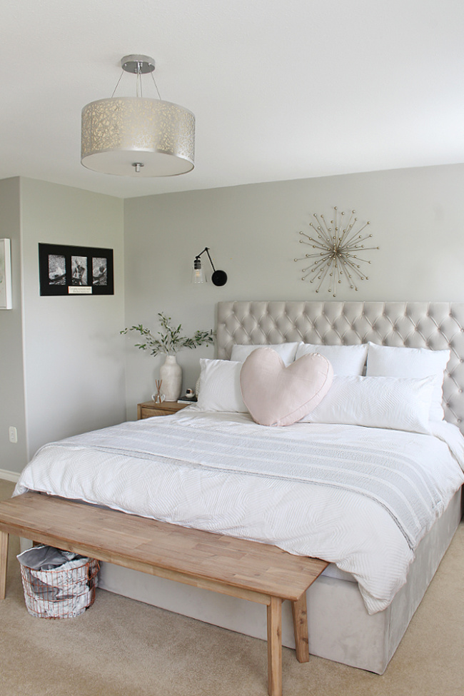 Master bedroom with grey upholstered bed and white bedding.