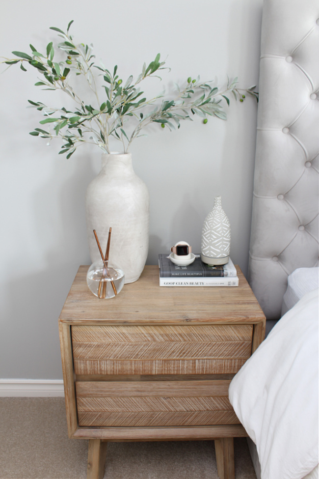 Bedside table decorated with a few simple decor pieces.