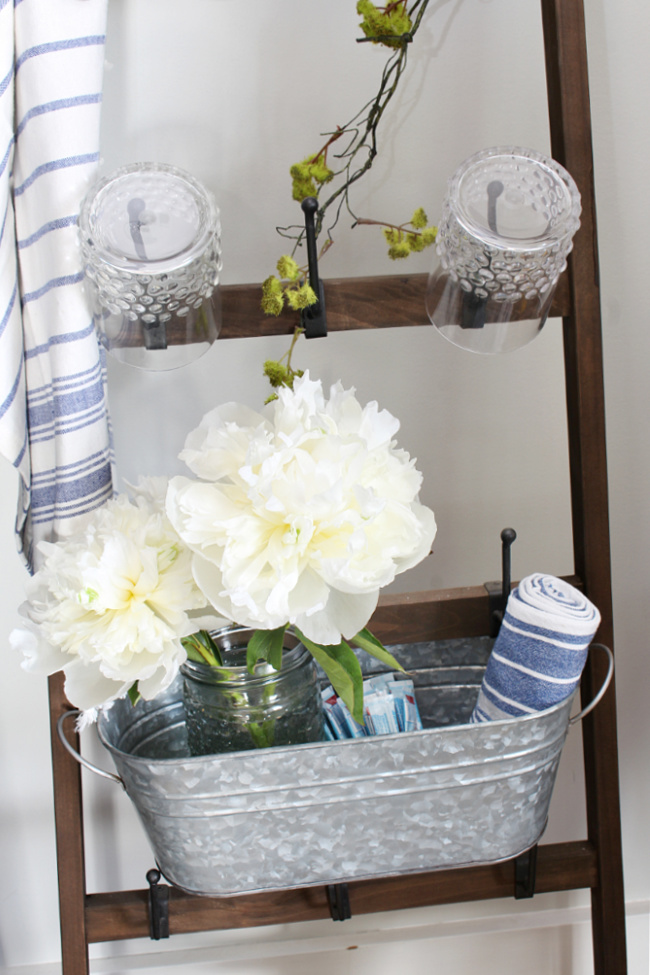 White peonies in a bucket on a mug ladder.