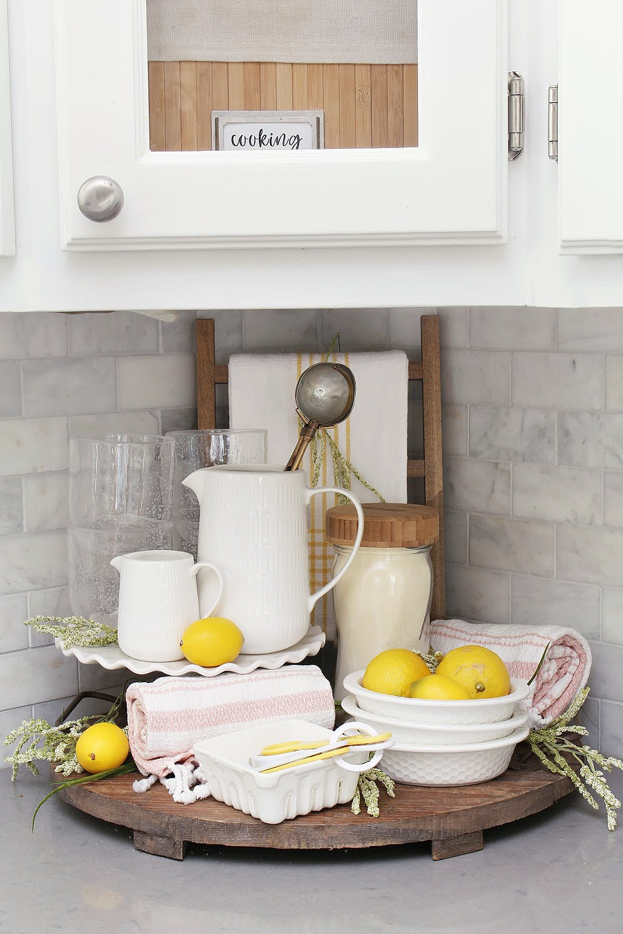 Summer kitchen decor using a wood tray, white dishware, and pops of yellow and pink.